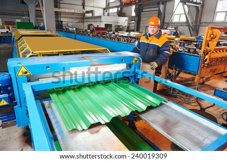 industrial worker operating metal sheet profiling mechine at manufacturing factory - stock photo