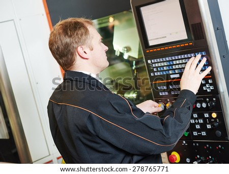 industrial worker programming cnc turning machine center for metal working at manufacture workshop - stock photo