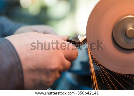 Industrial worker sharpening drill with grindstone abrasive disc cutter machine - stock photo