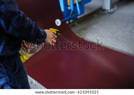 industrial worker spray on metal sheet profiling machine at manufacturing factory