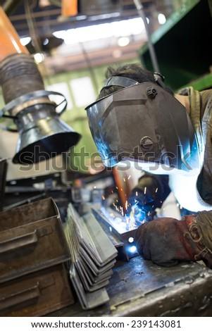 Industrial worker welder welding metal at factory workshop - stock photo