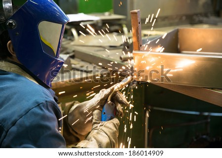 Industrial Worker Welder welding metal at factory workshop with flying sparks - stock photo