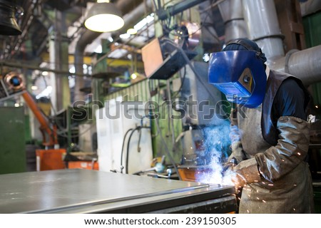 Industrial worker welding metal at factory workshop with flying sparks - stock photo