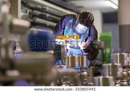 Industrial worker with protective mask welding inox elements in steel structures manufacture workshop.