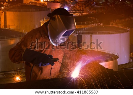 Industrial Worker with safety equipments and protective mask welding steel structure with Natural Oil and Gas storage tanks and in Petrochemical industrial plant at background  - stock photo
