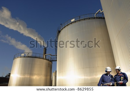 industrial-workers in front of refinery oil storage tanks, smoke and blue-sky in background - stock photo