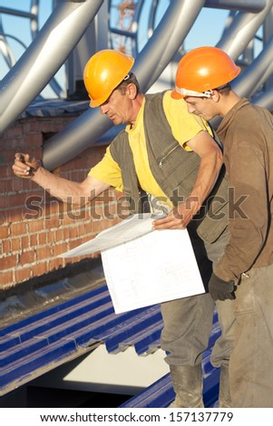 Industrial workers with blue print during construction works - stock photo