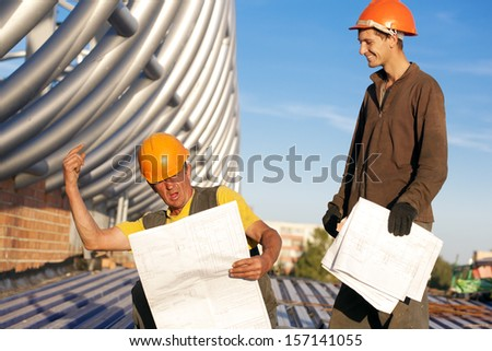Industrial workers with drawings during construction works - stock photo
