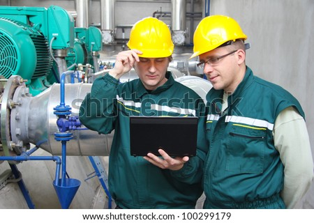 Industrial workers with notebook working in power plant, teamwork - stock photo