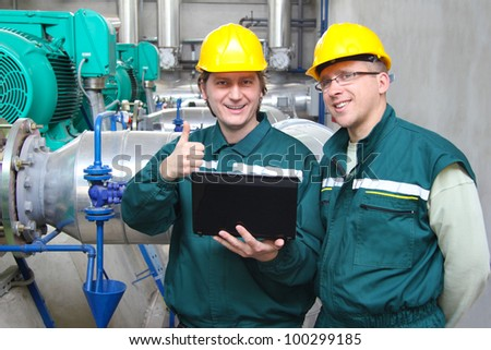 Industrial workers with notebook working in power plant, teamwork well done - stock photo