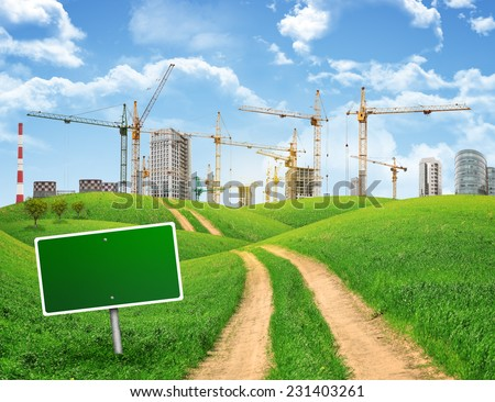 Industrial zone, green hills and road with empty road sign against sky with clouds. Business concept - stock photo