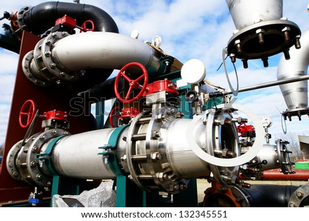 Industrial zone, Steel pipelines and valves against blue sky - stock photo