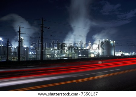 industry area with traffic and smoke stacks by night - stock photo