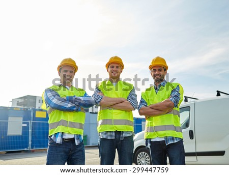 industry, building, construction and people concept - happy male builders in high visible vests outdoors - stock photo