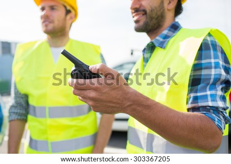 industry, building, technology and people concept - close up of male builders in high visible vests with walkie talkie or radio outdoors - stock photo