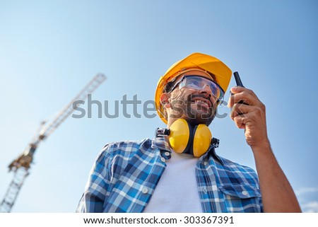 industry, building, technology and people concept - male builder in hardhat with walkie talkie or radio outdoors - stock photo