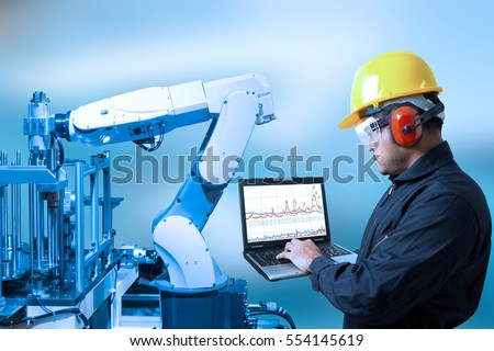 Industry concept and blue tone of Engineer programing automated robot arm in production line of smart factory