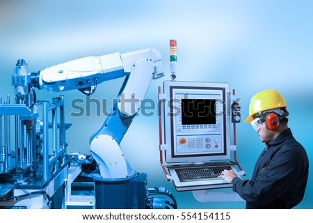 Industry concept and blue tone of engineer use control panel programing automated robot arm in production line of smart factory