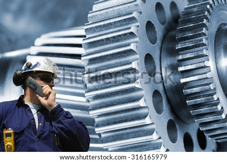 industry worker, mechanic with large gears and cogwheels machinery, blue toning - stock photo