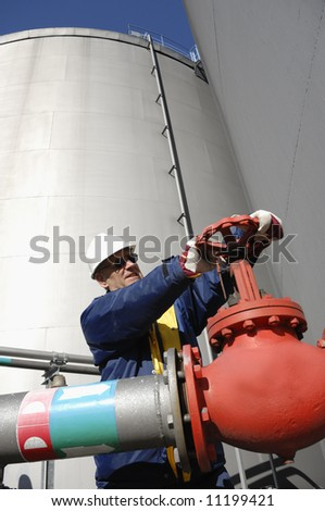 industry worker turning on pipeline and fuel pump inside oil industry - stock photo
