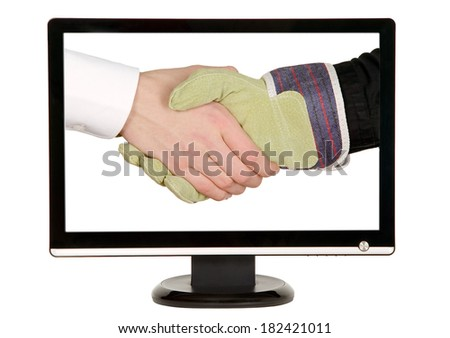 Industry worker with glove shakes hands with businessman on lcd monitor
