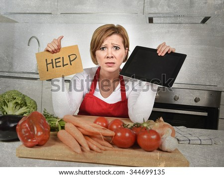 inexperienced home cook woman in red apron screaming desperate and frustrated at domestic kitchen in stress holding digital tablet asking for help in amateur and rookie cooking mess  - stock photo