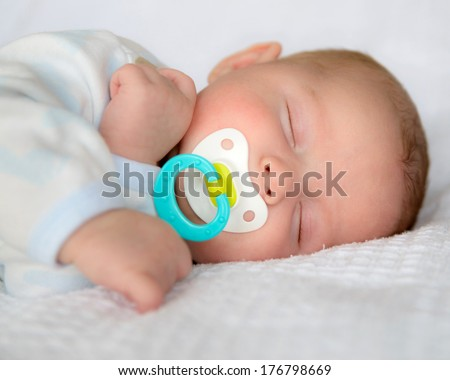 Infant baby boy sleeping peacefully with pacifier - stock photo
