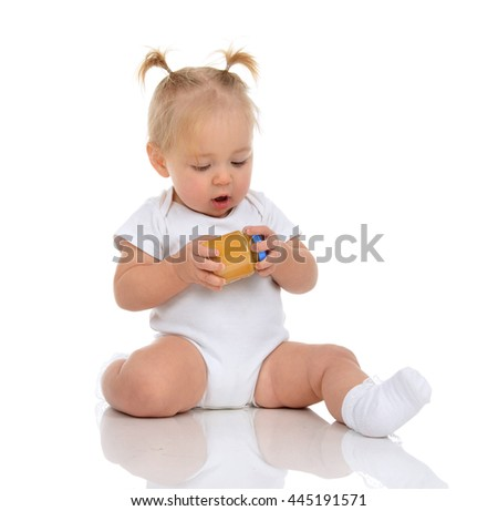 Infant Baby girl kid sitting and holding in hands jar of child mash puree food isolated on a white background
