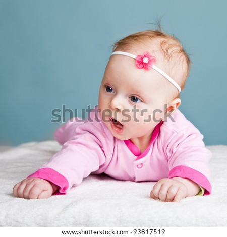 Infant baby girl raising head in funny