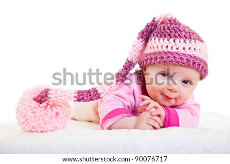 Infant baby girl raising head in funny hat isolated on white - stock photo
