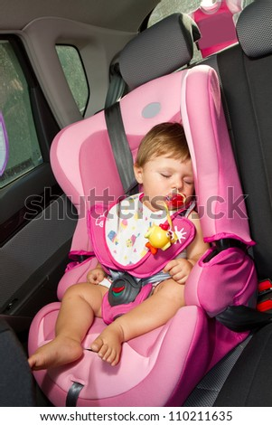 Infant baby sleeps peacefully secured with seat belts while in the car. - stock photo