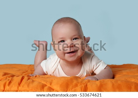Infant baby smiles crawling on orange blanket on blue background - Happy toddler, childcare concept