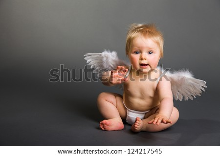 Infant baby with angel wings on neutral background - stock photo