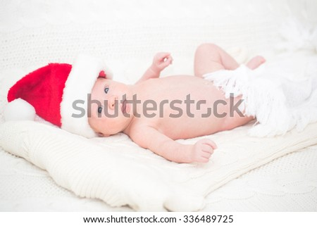 Infant boy in Santa hat laying on the bed