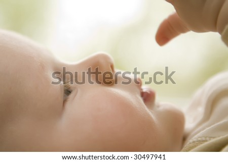 Infant boy looking at his hand with soft focus - stock photo