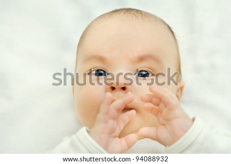 infant boy looks into the camera camouflage, hands