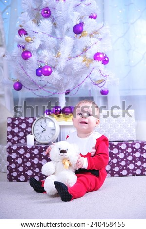 Infant boy sitting near New Year Tree in Christmas interior. Happy son having fun with Christmas presents. Kid Celebrate Holiday, Opening Present Gift Box. Christmas Family Portrait.  - stock photo