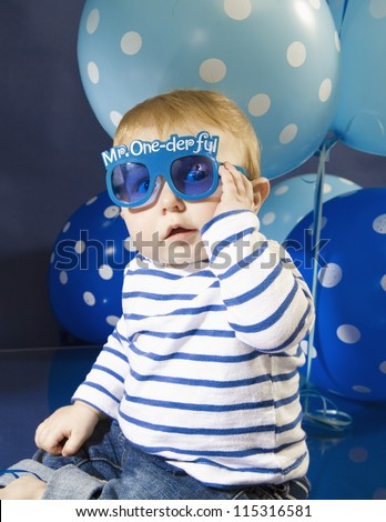Infant boy wearing fun party glasses celebrating his first birthday - stock photo