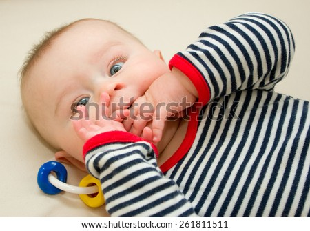 Infant boy with wide opened eyes laying in a bed with fingers in his mouth - stock photo