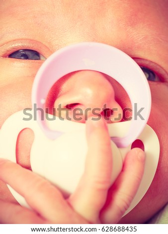 Infant care, beauty of childhood concept. Little newborn baby lying calmly in bed with teat in mouth, closeup.
