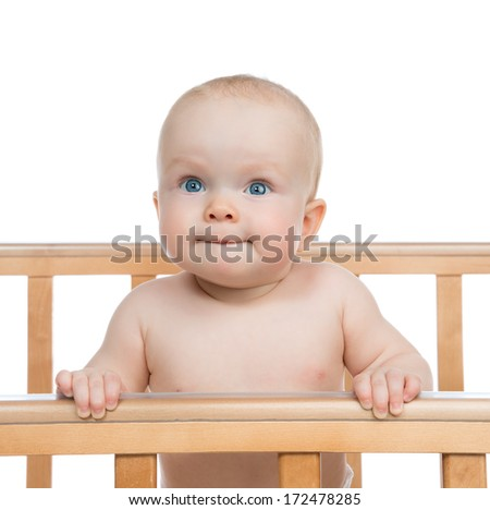 Infant child baby boy in wooden bed looking up on white background
