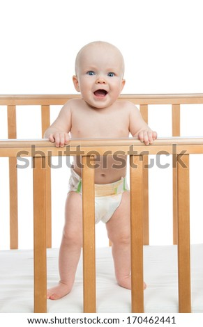 Infant child baby boy shouting or yelling in diaper in wooden bed on white background