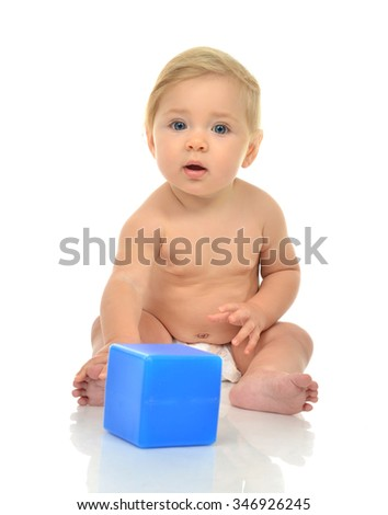 Infant child baby boy toddler playing holding blue brick toy in hands on a floor isolated a white background