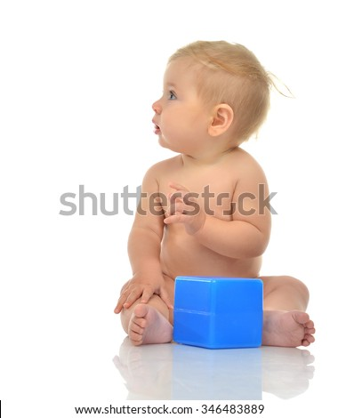 Infant child baby boy toddler playing holding blue bricks toy in hands on a floor on and looking straight isolated a white background