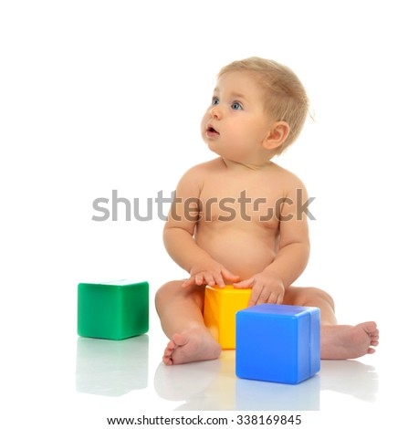 Infant child baby boy toddler playing holding green blue yellow bricks in hands on a floor on and looking up isolated a white background - stock photo