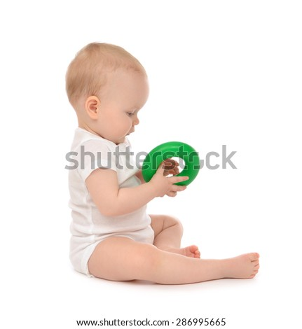 Infant child baby boy toddler playing holding green circle in hand on a floor on and looking up isolated a white background - stock photo