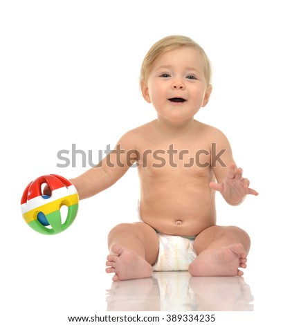 Infant child baby boy toddler playing holding green red yellow ball in hands on a floor on and looking up isolated a white background