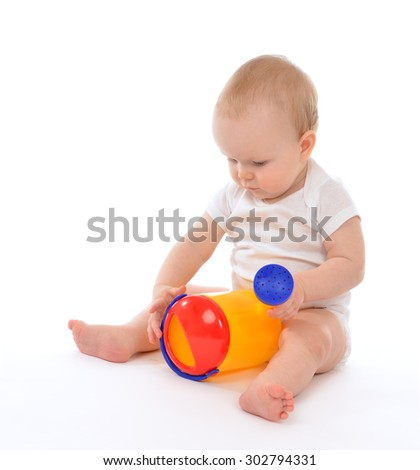 Infant child baby boy toddler playing holding watering can in hand on a floor on and looking up isolated a white background