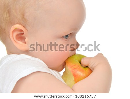 Infant child baby girl eating apple closeup isolated on a white background