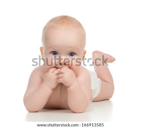 Infant child baby girl in diaper lying happy smiling and eating hands on a white background - stock photo